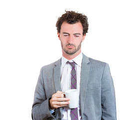 Sleepy business man after long working hours holds cup coffee