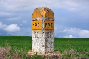 señal de trafico de piedra amarilla en carretera comarcal
