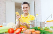 woman in yellow cooking  with pasta