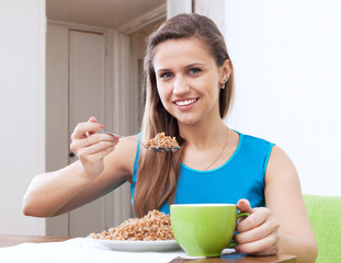 Smiling woman eats buckwheat cereal