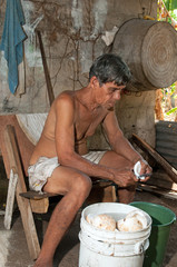 native senior man cleaning slicing fresh coconut for production