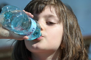 Portrait Of A Beautiful Thirsty Little Girl Drinking Water
