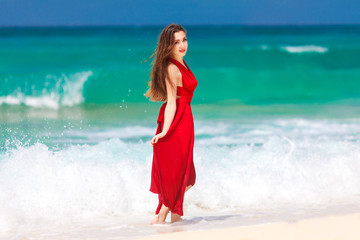 beautiful woman in a red dress  standing on the tropical sea co