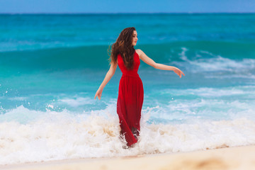 beautiful woman in a red dress on the tropical sea coast