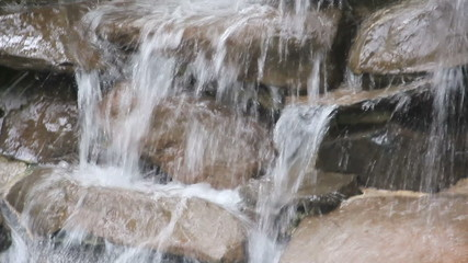 Water falling on rocks and slate in a poolside water feature.