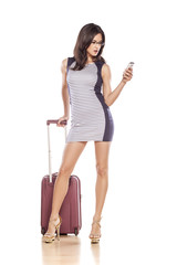 beautiful brunette writes text message next to her suitcases
