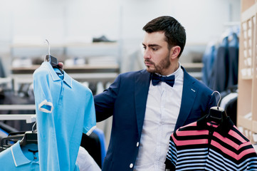 Attractive young  man chooses tee - shirt at a shop.