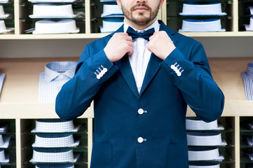 Handsome young man in classic suit against showcase with shirts