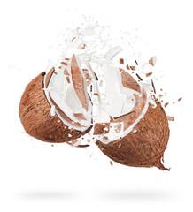 Coconut with milk splashes on white background