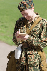 Military female writing in notebook outdoor