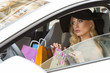 elegant girl in car with shopping bags