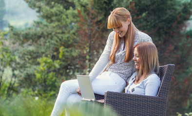 Two girlfriends sitting outdoors and using laptop