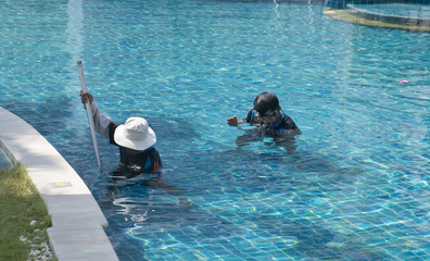 Workers cleaning a swimming pool