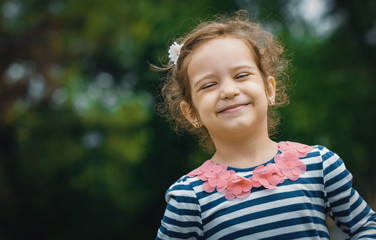 Portrait of cute little girl in a park with closed eyes