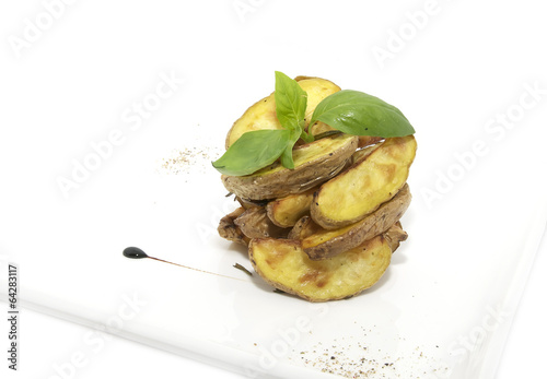 Baked potatoes on a plate decorated with greens