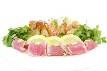 shrimp and tuna with greens and sauce on a white background