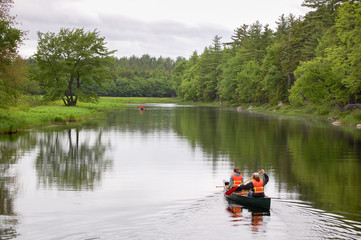 People Canoeing in a Park on a Cloudy Day