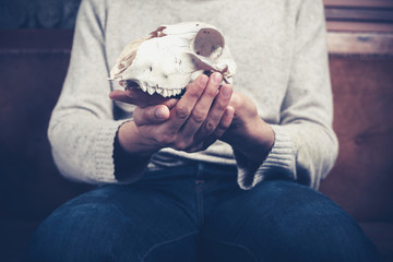 Man sitting on sofa with a skull in his hands