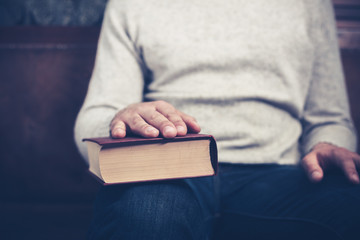 Man sitting with his hand on a book