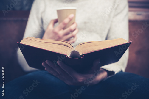 Man reading and drinking from paper cup - 64285595