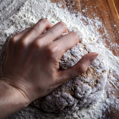 female hand knead the dough for bread