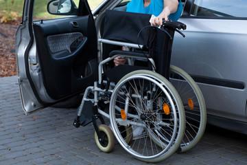 Man packing wheelchair into a car