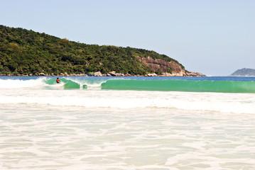 Surfer on Praia Lopes Mendes beach at Ilha Grande Island Brasil