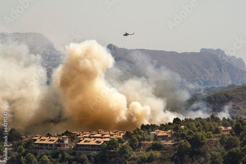 Helicopter in a fire burning mountain forest and village, danger