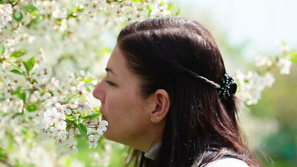 women smelling white flowers in springtime