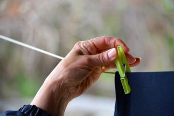 manos de mujer mayor tendiendo la ropa con pinzas