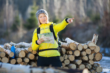 Woman hiking in winter forest with map