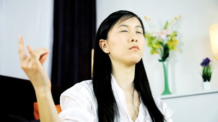 Asian woman praying and meditating at home