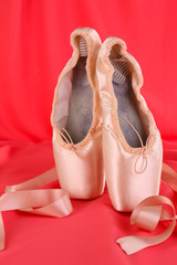 Ballet pointe shoes on red fabric background