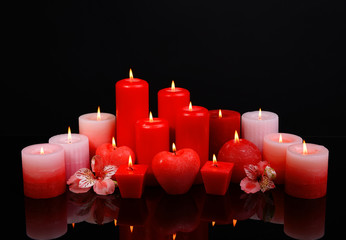 Beautiful candles with flowers isolated on black