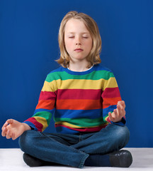 Young boy practicing yoga meditation