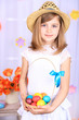Beautiful small girl holding basket with colorful eggs