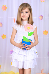 Beautiful small girl holding flower in pot