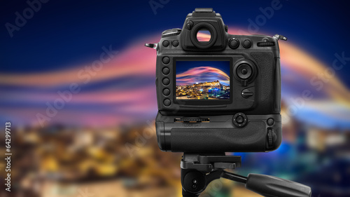 Foto op Canvas Europa DSLR Camera on tripod shooting night city with aurora borealis