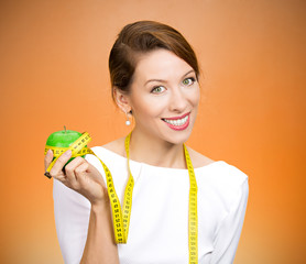 Fit options. Happy young woman holding apple, measuring tape