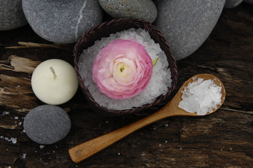 spoon and ranunculus flower , stones ,candle on driftwood wood