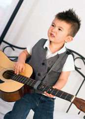 Young Boy Jamming Full Size Guitar Gritting Teeth Playing Music