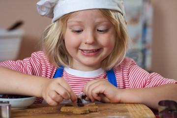 Cute smiling boy putting raisins on gingerbread
