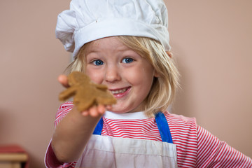 Cute proud boy holding up gingerbread man