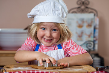 Cute smiling boy baking gingerbread