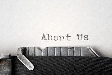 """About Us"" written on an old typewriter"