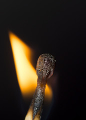 Close up burning matchstick on black background