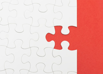 Incomplete white puzzle with red color background with copyspace