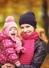 Mom and baby daughter for  walk in autumn