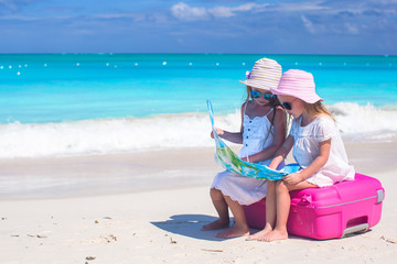 Little lovely girls sitting on big suitcase and a map at