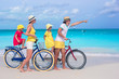 Young family riding bicycles on a tropical beach